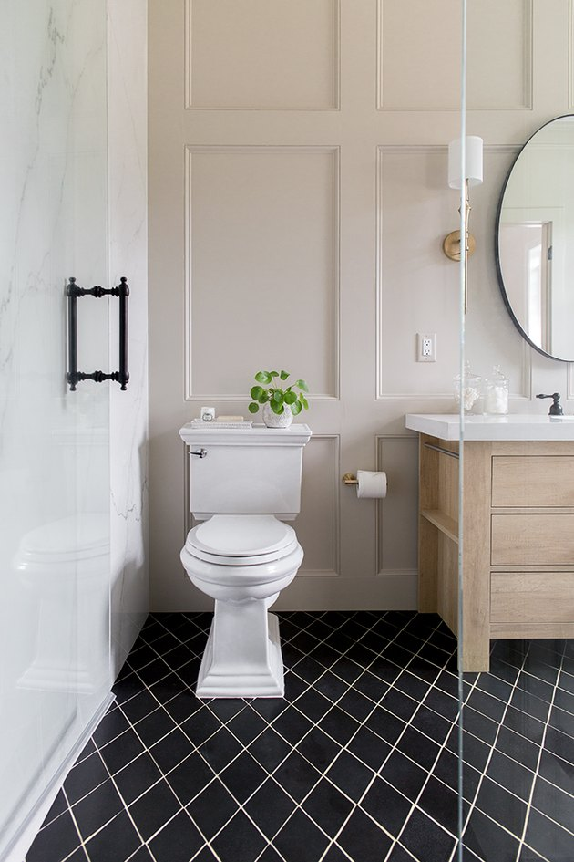 A two-piece type of toilet in a traditional neutral bathroom