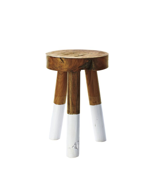Small raw wood stool with three legs, the lower half of which are dipped in white paint