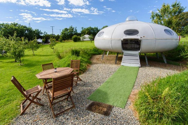 outdoor photo of patio area with table and chairs and UFO-shaped structure