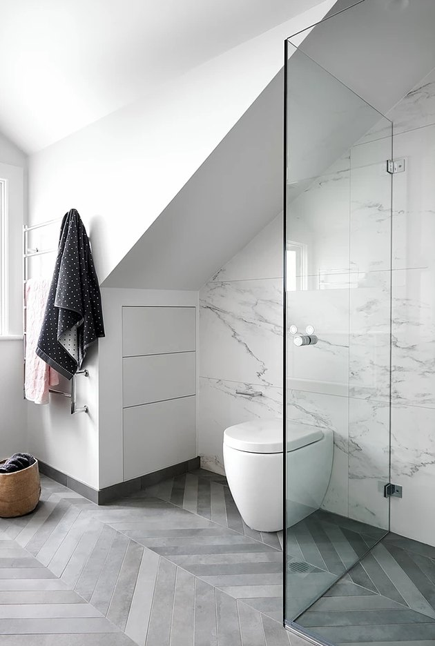 A wall-mounted type of toilet in a modern white bathroom