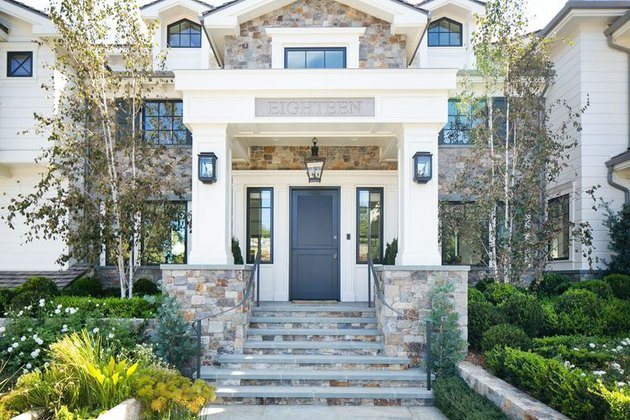 Stone Exterior Homes with white siding home by Kelly Nutt Design