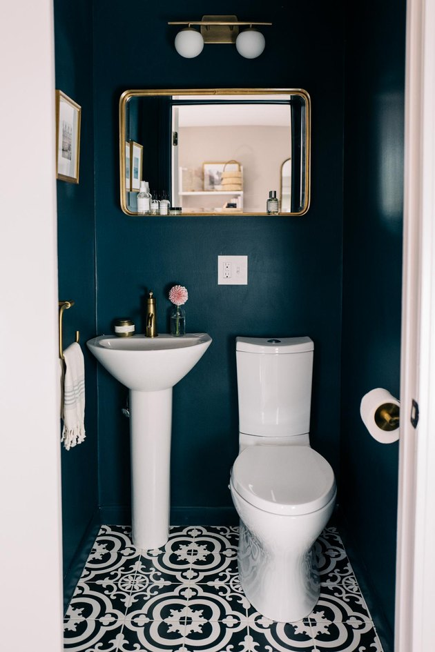 Geometric bathroom pedestal  sink with blue walls and patterned floor tile