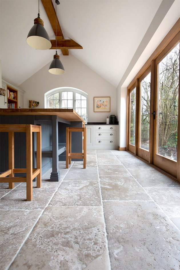 limestone kitchen flooring with wood accents and blue island