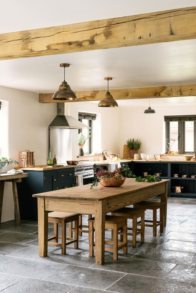 limestone kitchen flooring with dark cabinets and exposed ceiling beams