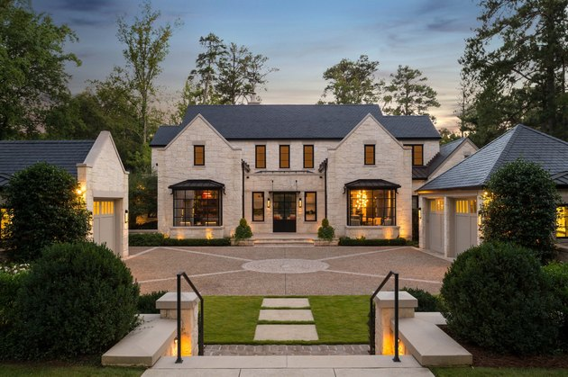 Stone Exterior Homes with stone garage and driveway by TS Adams Studio