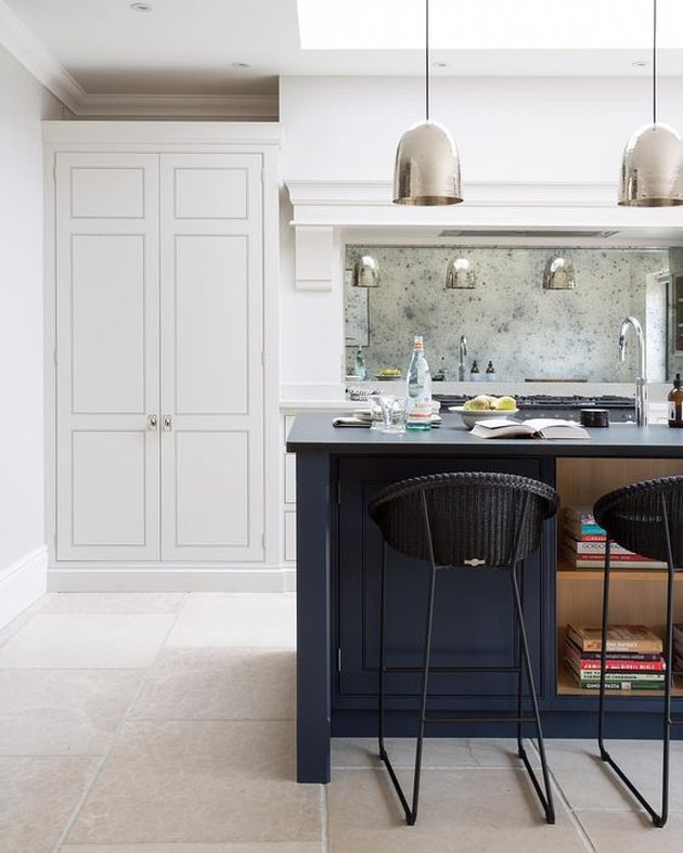limestone kitchen flooring with blue island and white cabinets paired with mirror backsplash