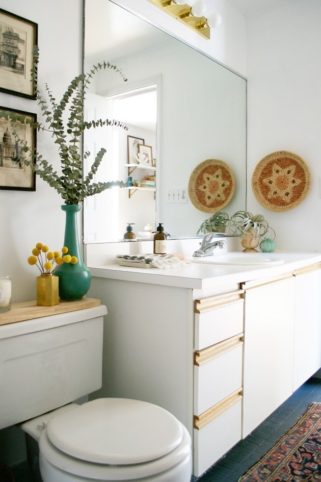 self-rimming bathroom sink in a boho rental with frameless mirror and white vanity cabinet