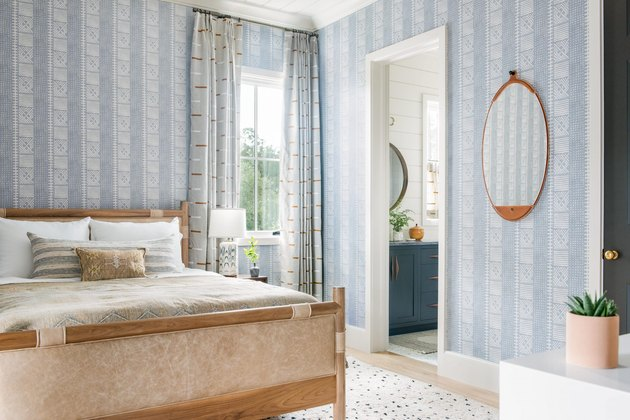 periwinkle wallpaper and leather bed in coastal bedroom