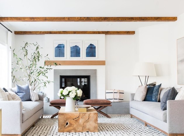white living room with coastal fireplace and wooden beams