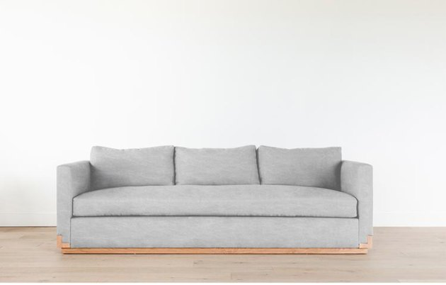 masculine coastal sofa with wood base detail in gray fabric