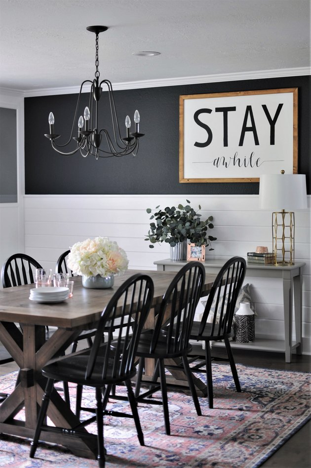 dark farmhouse dining room with iron chandelier and white shiplap walls
