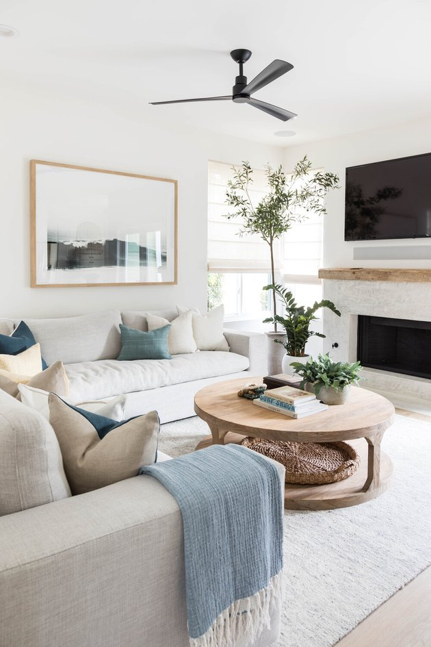 white living room with coastal fireplace white sofas and ceiling fan