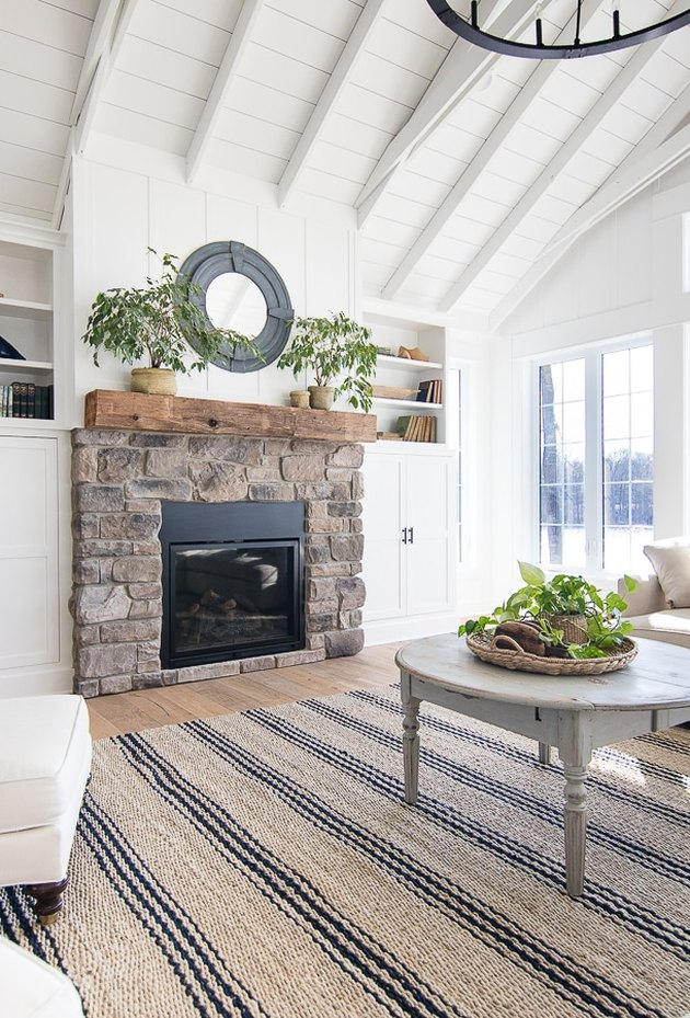 white living room with coastal fireplace made of stone with porthole mirror above
