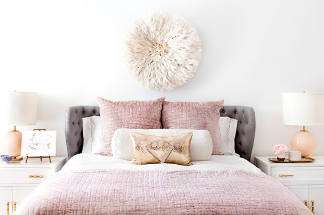 bedroom with light pink bedding and tufted gray headboard