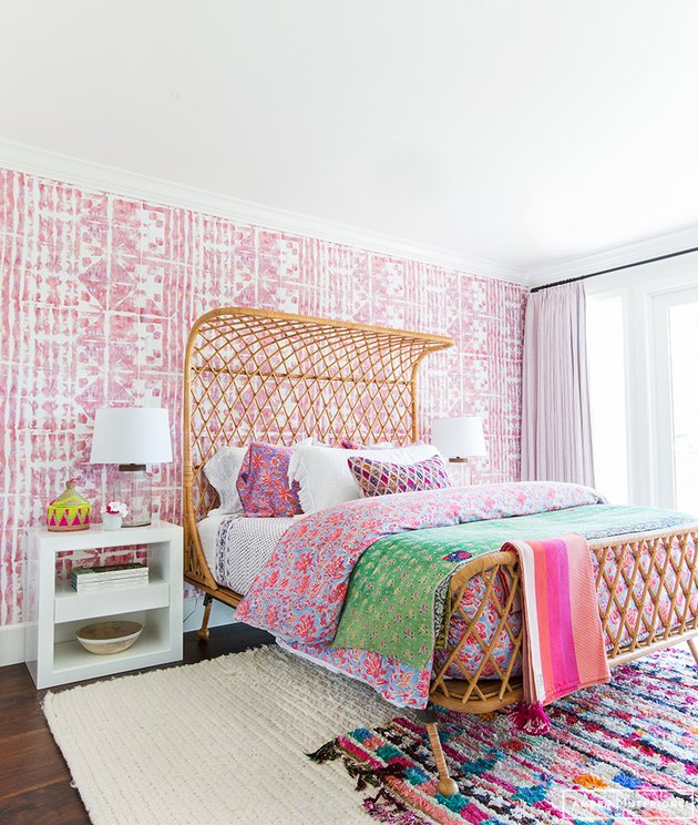 pink bohemian bedroom with woven rattan bed and pattern wallpaper