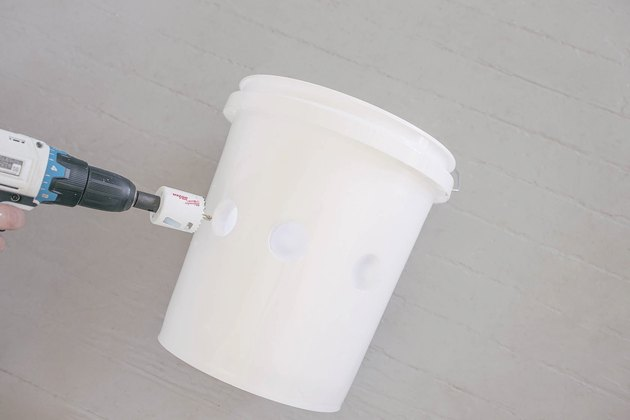 Drilling three holes in front of plastic bucket with hole saw