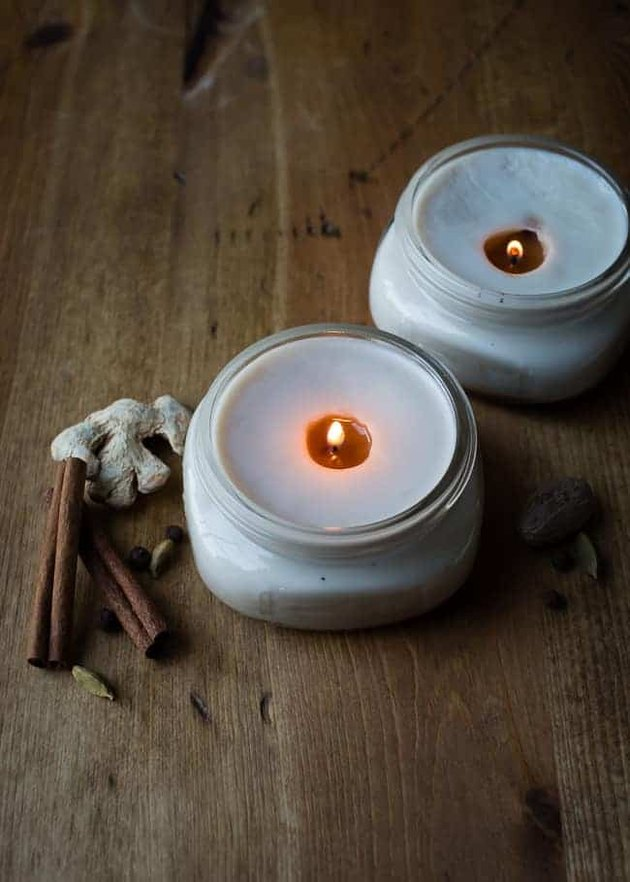 DIY fall decor idea with lit white candles on wood floor