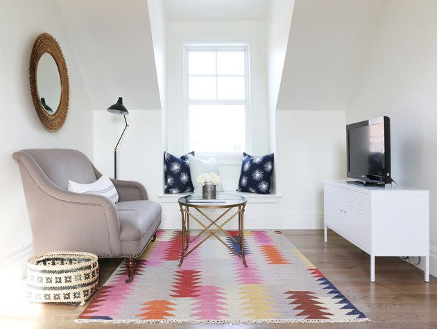 white finished attic idea for tv room with sofa and colorful rug
