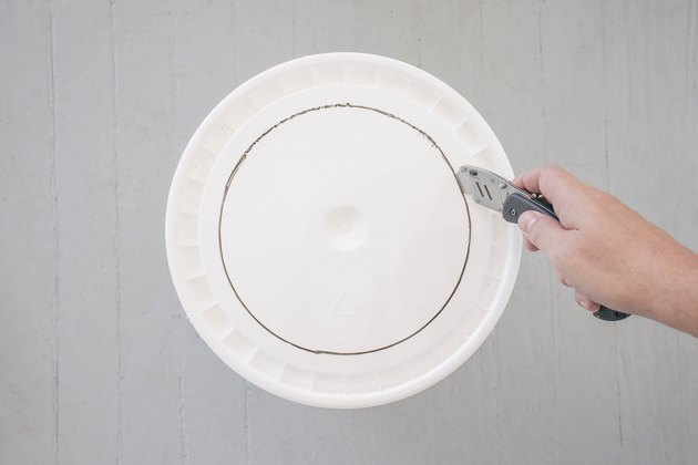 Cutting out circle on bucket lid with a box cutter