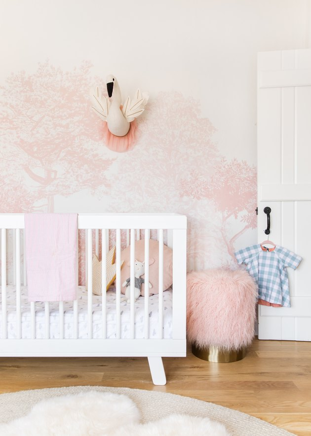 pink-and-white wallpaper in a nursery with white crib