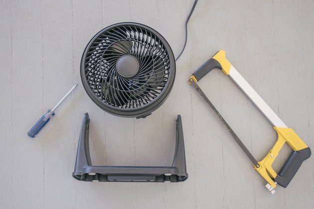 Black table fan with its stand removed next to screw driver and hacksaw
