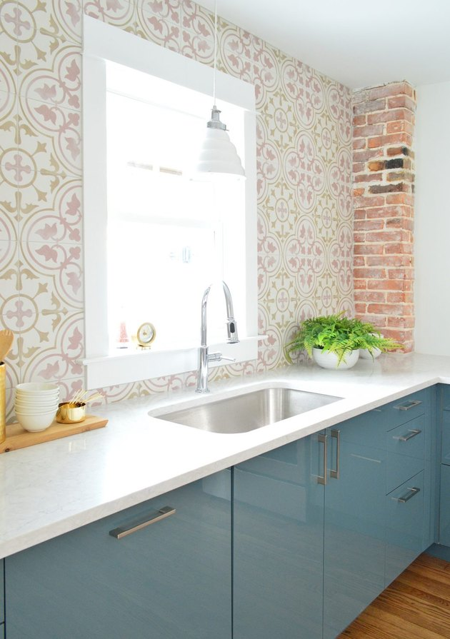 Pink and white floral coastal backsplash in kitchen with blue cabinets