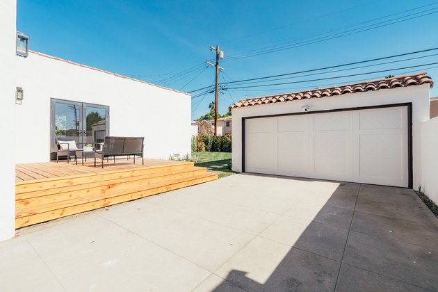 A white garage with a Spanish-style roof, a concrete driveway that is next to a wooden deck
