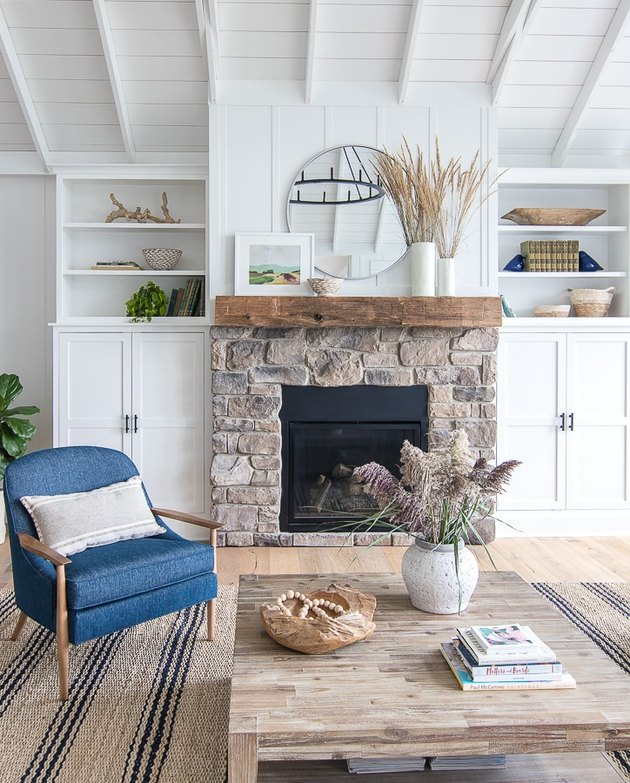 Coastal fall decor in coastal style living room with stonework fireplace and dried grasses