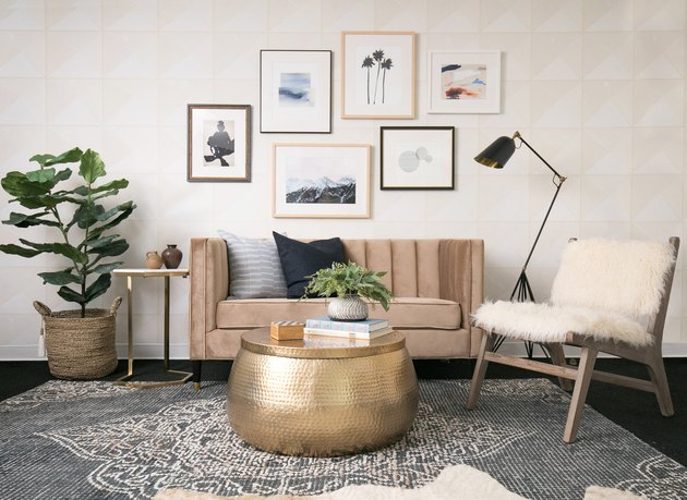 neutral wallpaper in a living room with channel tufted sofa and gallery wall