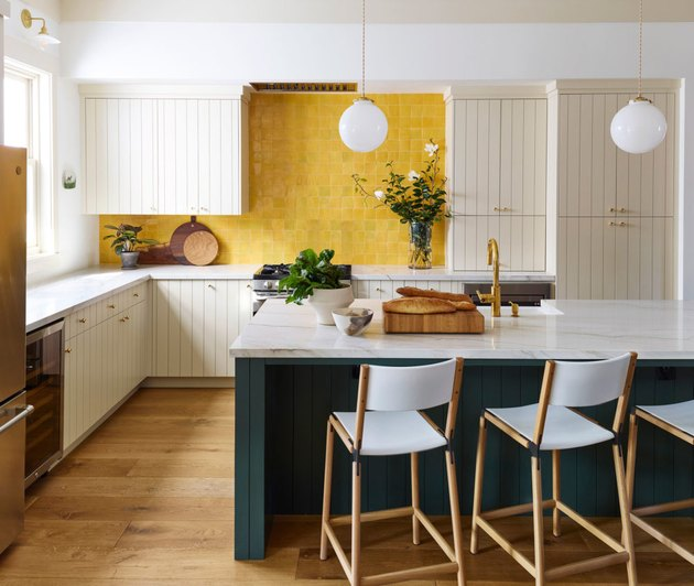 Yellow Room Ideas in Yellow tile backsplash, off white cupboards, white bar stools, kitchen island, white globe pendant lamps.