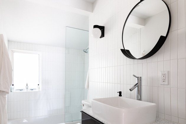 White bathroom with vertical white tiles and black mirror