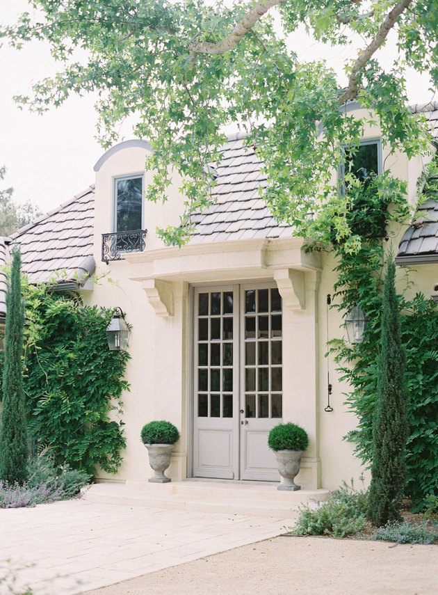 French country exterior with French doors and lush greenery