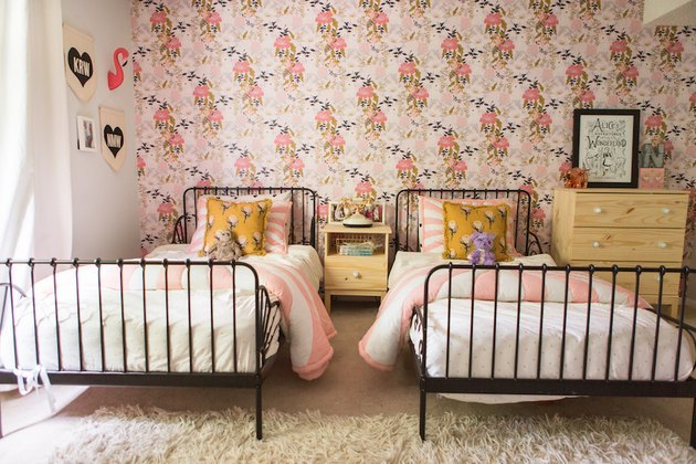pink room ideas with Floral wallpaper, twin brass beds, multi-colored bedding.