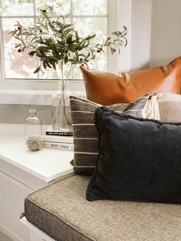 modern fall decor for sofa nook with pillows and a vase of olive branches