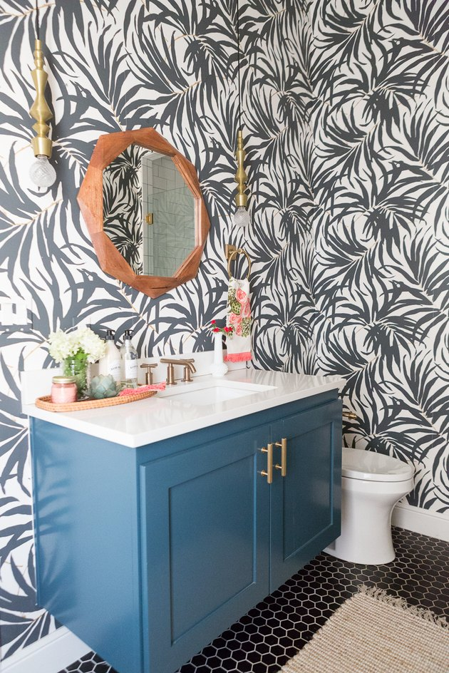 Beachy bathroom wallpaper with black and white palm print and blue vanity cabinet