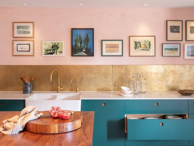 pink room ideas with Pink walls, gold backsplash, teal cupboards, wood counter, brass sink faucet in kitchen.