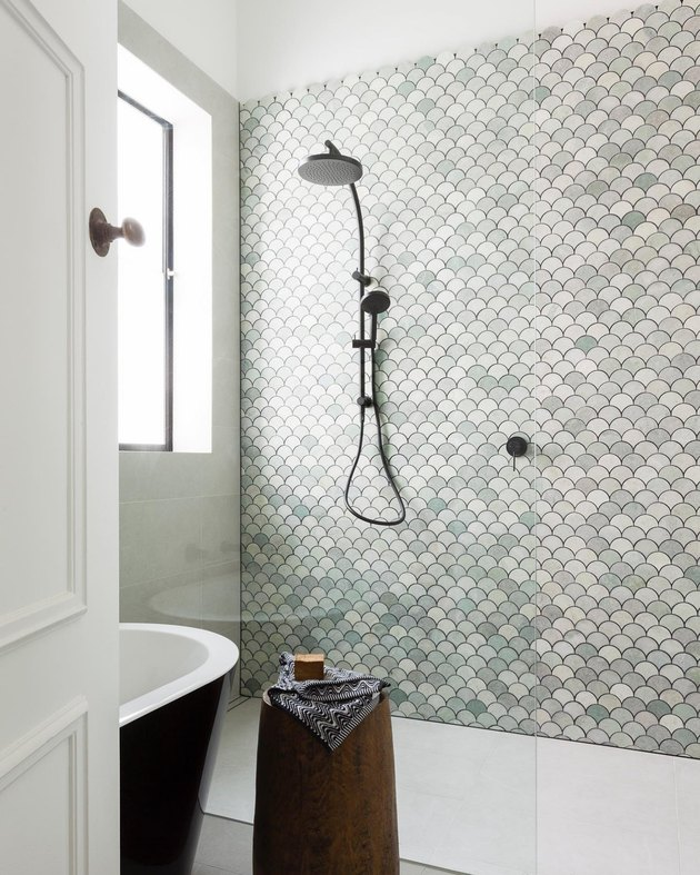 Handheld showerhead in open shower with green mosaic wall tile