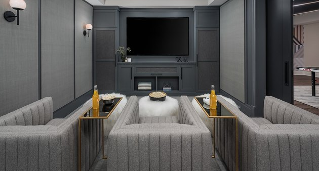 basement ideas with Gray lounge chairs, gray walls and flat screen tv in screening room.