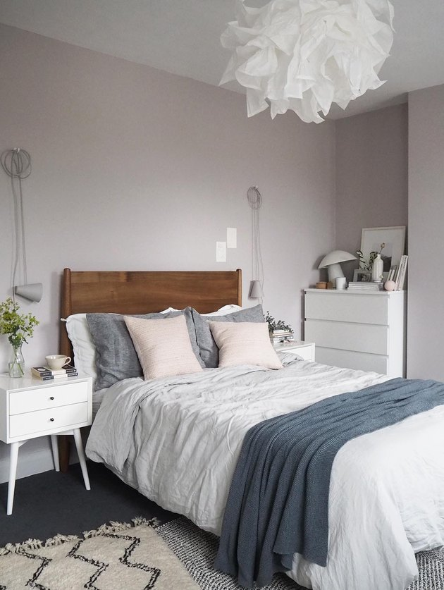 blush pink bedroom with blue bedding and white pendant