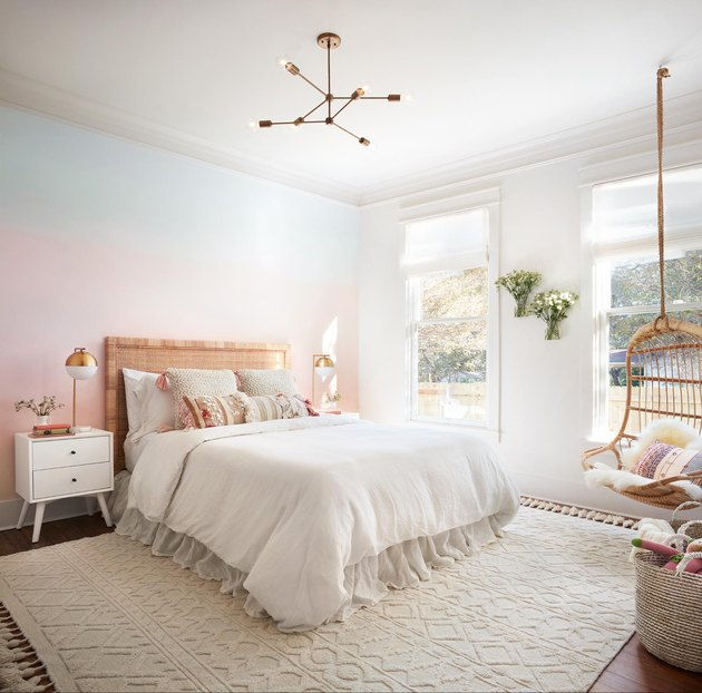 pink ombré wall in little girls bedroom with hanging chair and kids nightstand