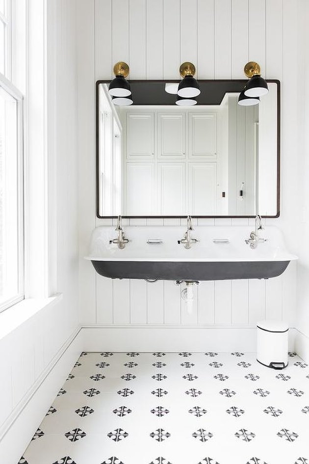 black and white patterned tile bathroom with trough sink