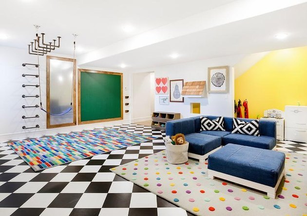 basement ideas with Black and white checker floors, multi colored area rug, navy blue sectional, yellow accent wall, chalkboard, climbing wall and ceiling.