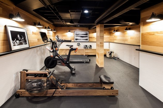 basement ideas with Gym equipment, rowing machine, bike, weights, padded flooring, black and white photos, light wood paneled and white walls.