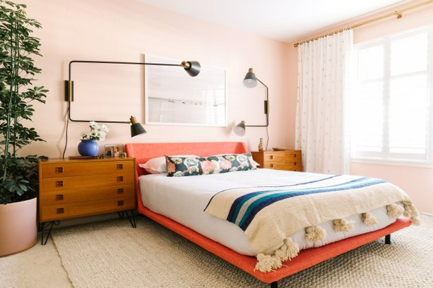 pink bedroom with coral bed and modern wall sconces