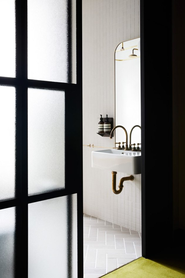 cement wall-mounted bathroom sink with gold gooseneck faucet