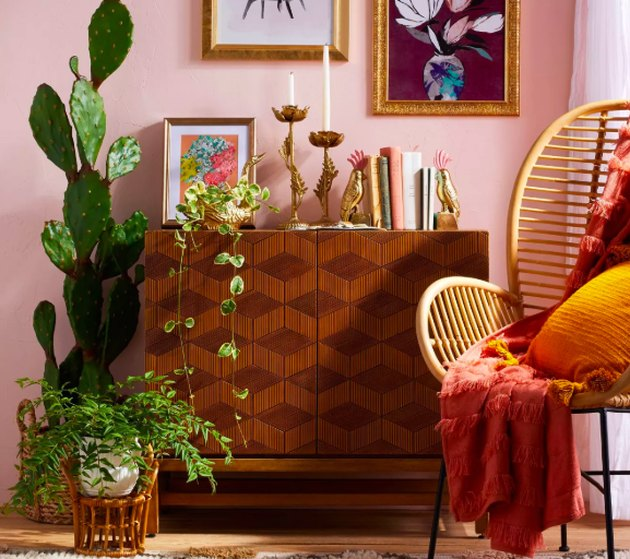 bookshelf, plant and chair with art and pillows