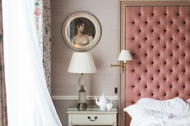 pink bedroom with tufted headboard and pink wallpaper