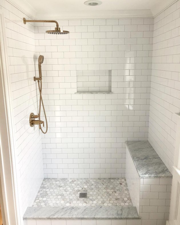 Brass handheld showerhead with rain shower and white subway tile