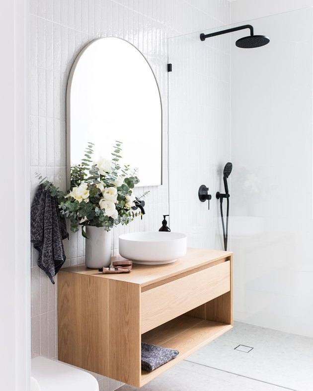 Black handheld showerhead and rain shower in white modern bathroom