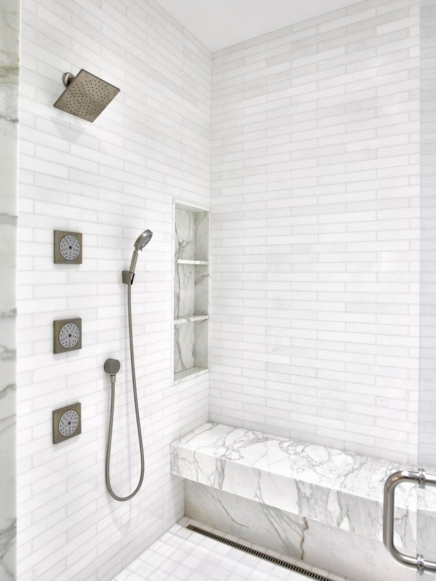 White marble shower with body sprays and handheld showerhead